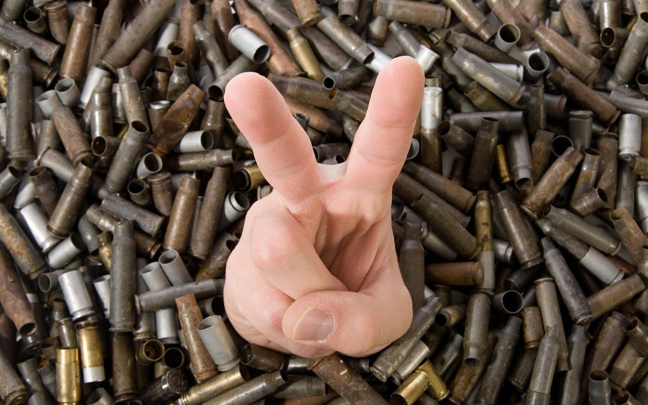 victory hand sign surrounded by bullet casings
